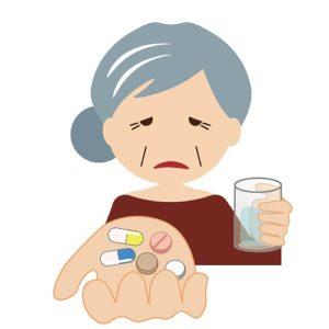 薬を飲もうとするきつそうなおばあさん