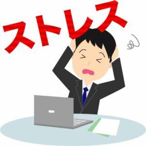 仕事のストレスで頭を抱える男性